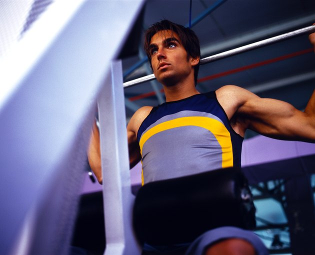 Low angle view of a young man lifting weights