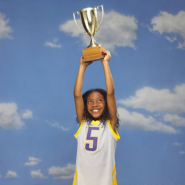 Basketball player holding trophy overhead