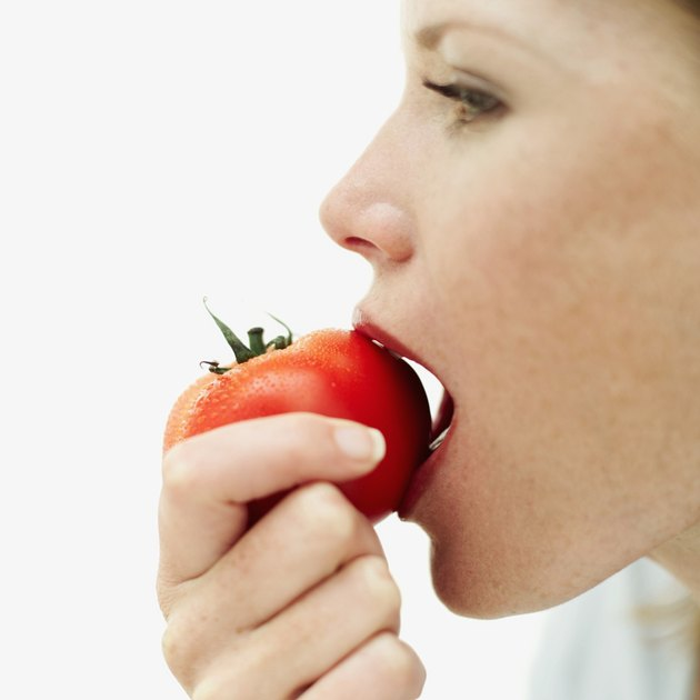 side profile of a young woman biting into a tomato