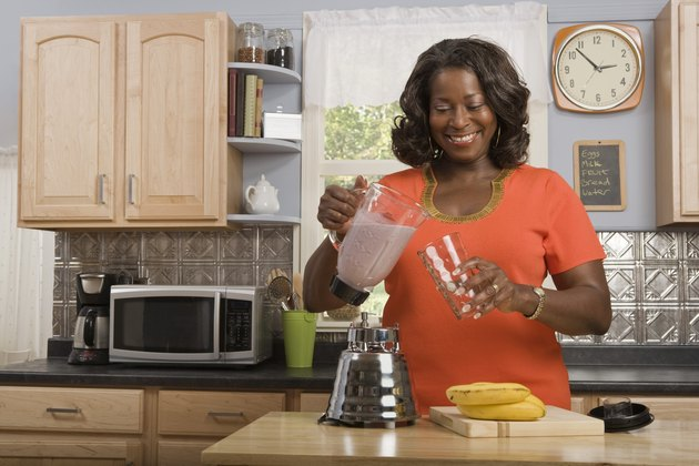 Woman in kitchen making smoothie