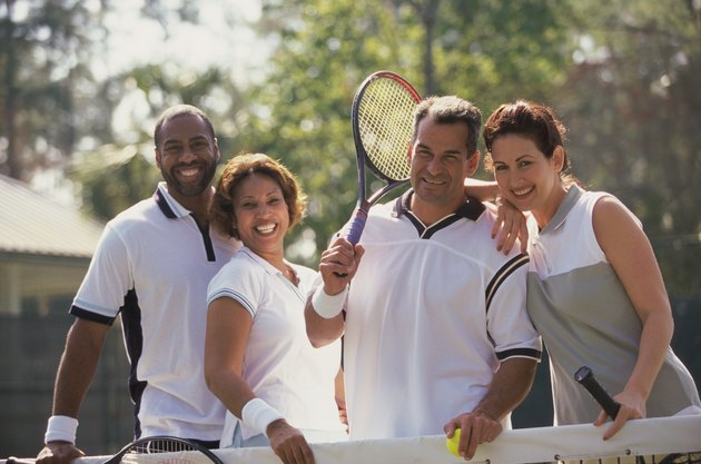 Portrait of two mid adult couples smiling on a tennis court