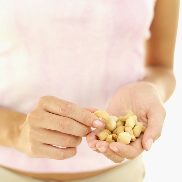 Young woman holding cashew nuts in her hand