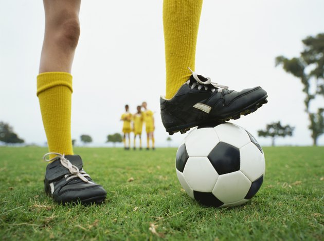 low section view of a person with his one leg on a soccer ball