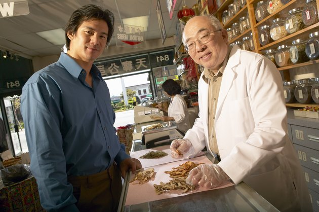 Chinese-herbalist in store with customer, portrait