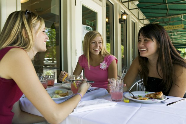 lifestyle portrait of a group of three teenage female friends as they hang out and eat at a cafe