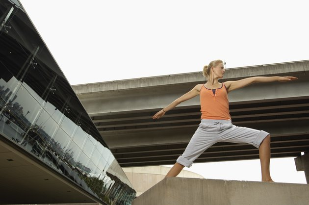 Young woman doing warrior 2 pose on concrete block, low angle