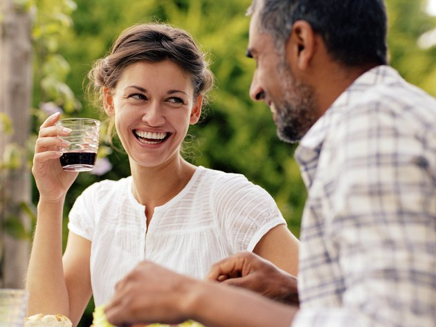 Couple dining outdoors, woman looking at man, laughing