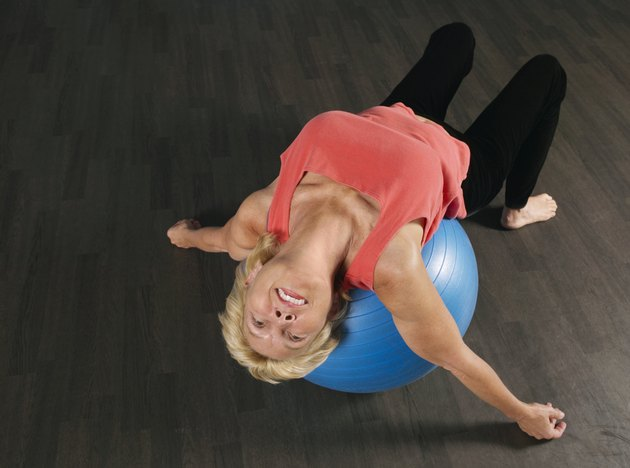 Mature woman using exercise ball, tilting head back, smiling