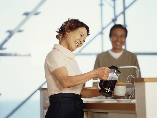 Senior woman pouring coffee in kitchen, senior man standing in background