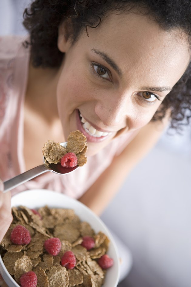Woman eating bowl of cereal, smiling, portrait, close-up