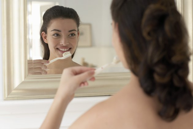 Young woman holding toothbrush, smiling, reflection in mirror