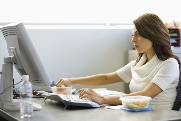 Young businesswoman eating lunch at desk