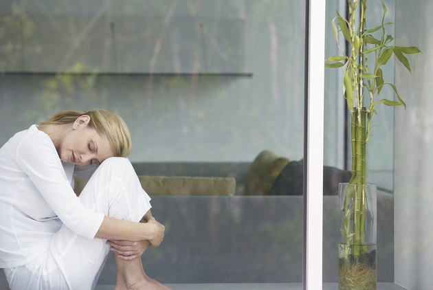 Woman relaxing by window, head on knees, view from outside