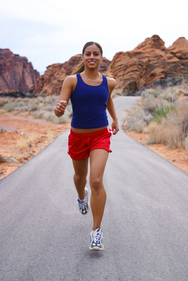 shot of a young ethnic female athlete as she runs through a rural red rock setting