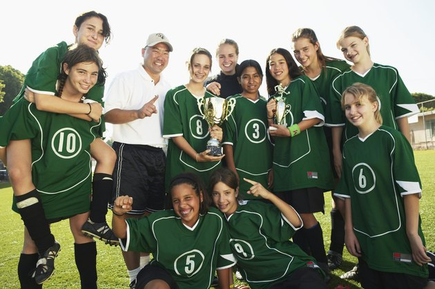 Football team (12-14) and coach with trophies, smiling, portrait