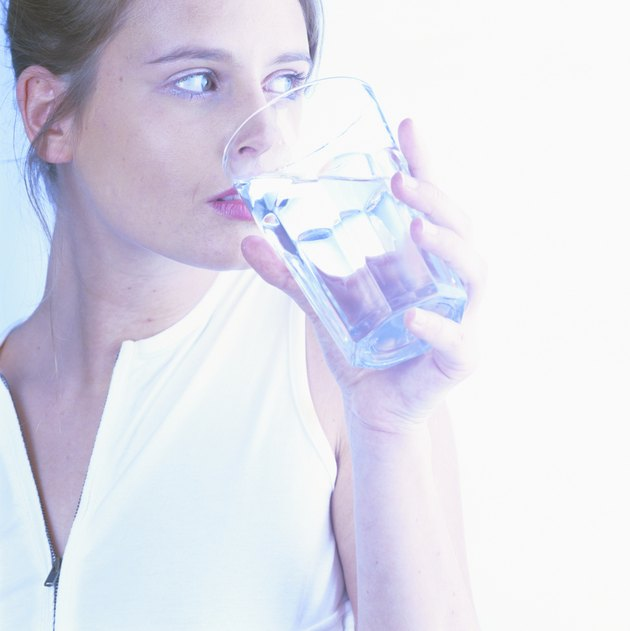Woman holding glass of water (cross-processed)