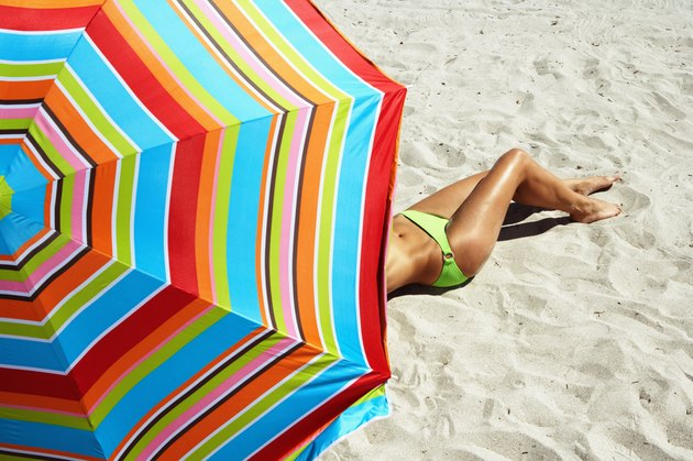 Young woman lying under beach umbrella, elevated view