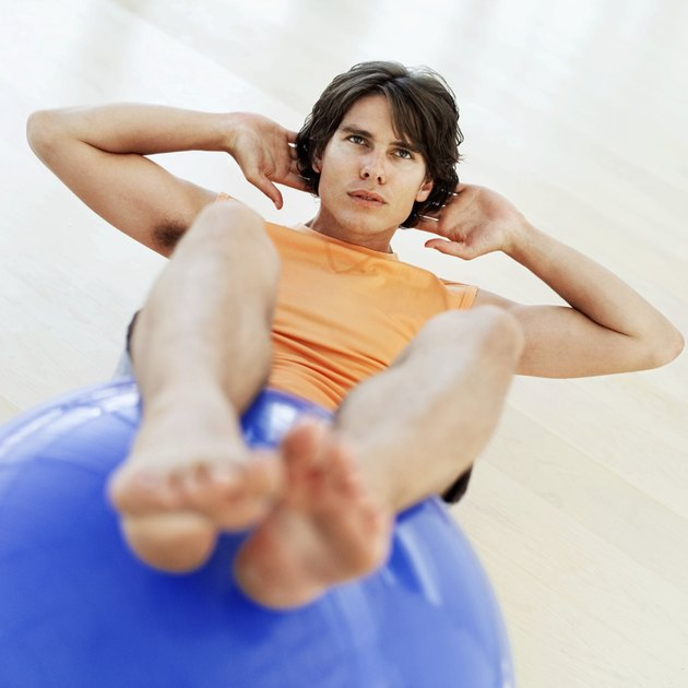 Elevated view of a man doing sit-ups with his legs on a ball