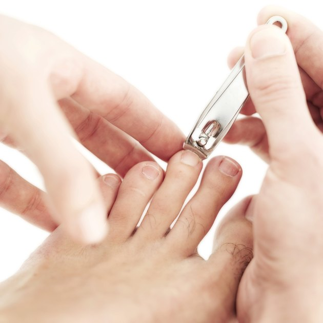 close-up of hands clipping toenails with a nail cutter