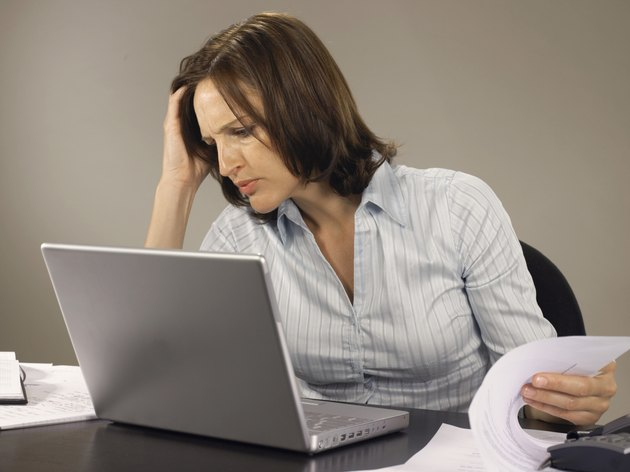 Woman using laptop resting head on hand, while turning page, frowning