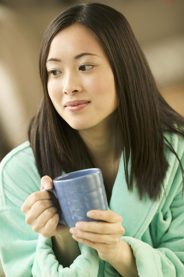 Young woman sitting holding a cup