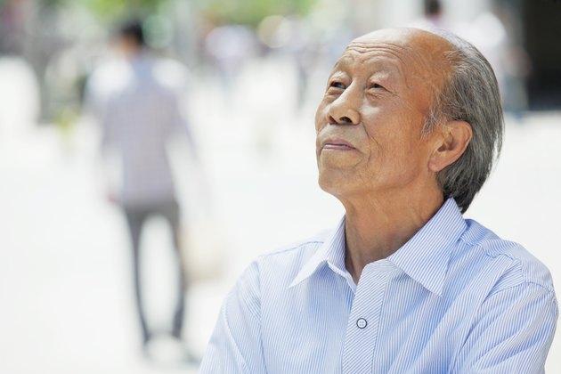 Portrait of smiling senior man, outdoors in Beijing