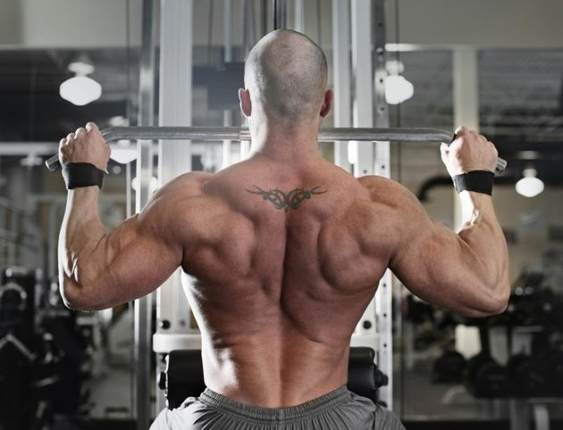 active and muscular man keeping his arms and back strong and fit by using gym equipment machinnes - filtered image