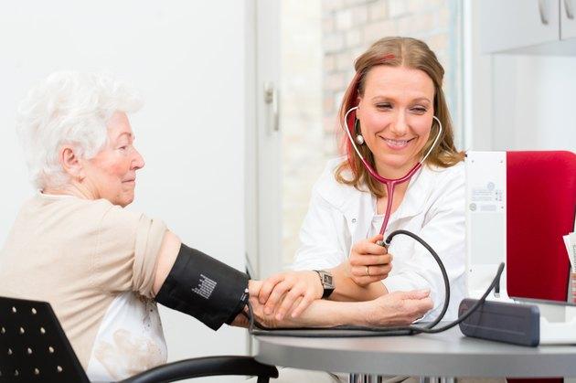 doctor measuring blood pressure of senior patient