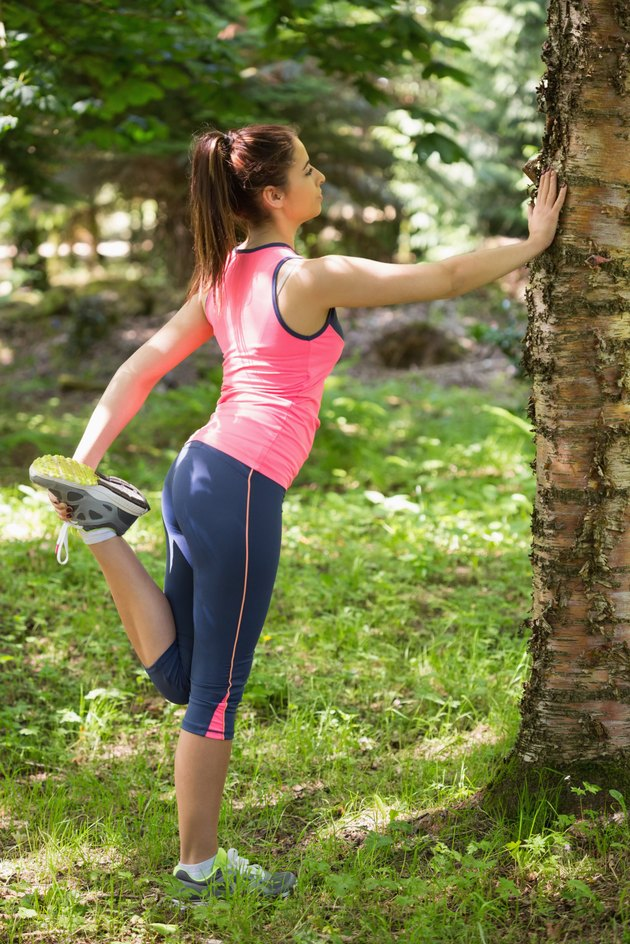 Sporty brunette woman stretching in a forest