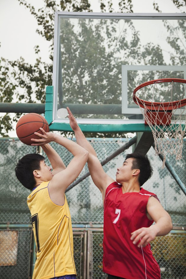 Two people playing basket ball