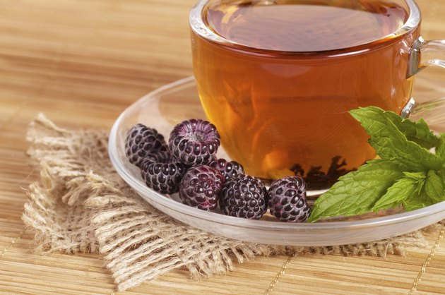 Fruit tea in cup with blackberry