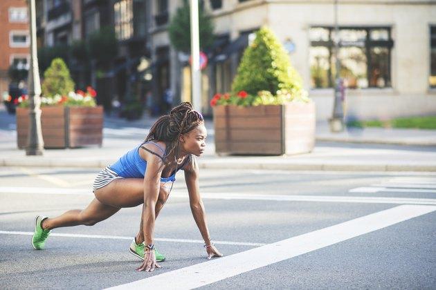 Beautiful african sport woman ready to run on the street.