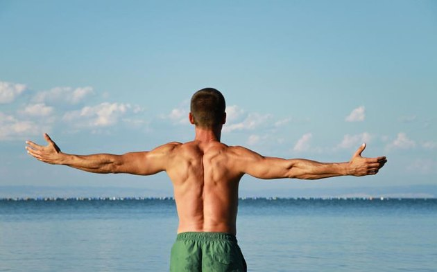 Man Raising His Hands or Open arms, looking to sea blue sky horizont. Strong muscular man, perfect body, arms, back. Freedom Concept