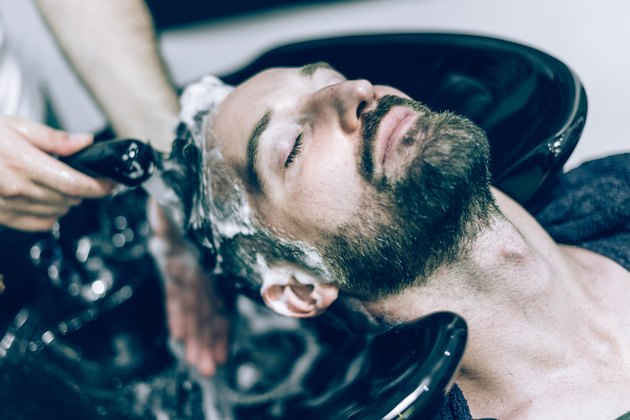 relaxed bearded man receives hair shower