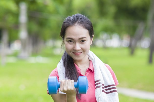 Fitness woman lifting dumbbell weight training outside