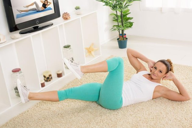 Beautiful young woman doing sit-up at home in front of the tv.