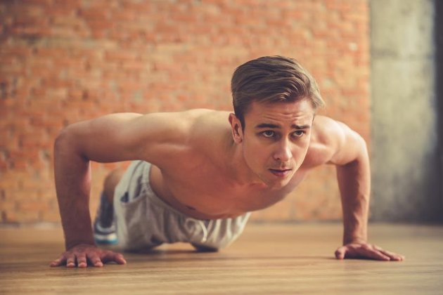 Handsome sportsman is doing push ups while working out in modern fitness hall