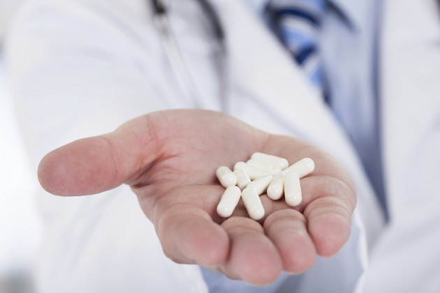 Male Doctor Holding Pills In Hand