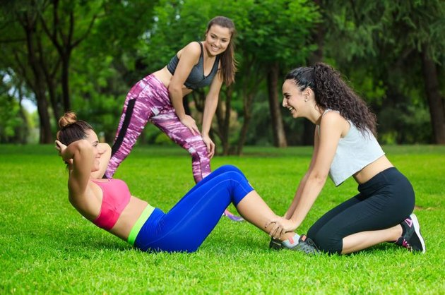 Healthy friends training in park on grass