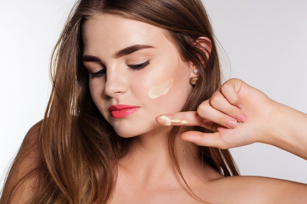 Girl is applying facial cream to cheek