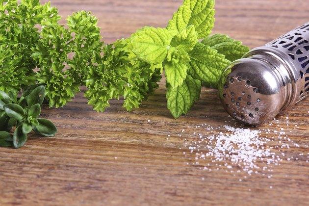 Salt cellar and herbs on a table