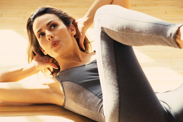 Woman lying on back in gym, doing calisthenic exercise