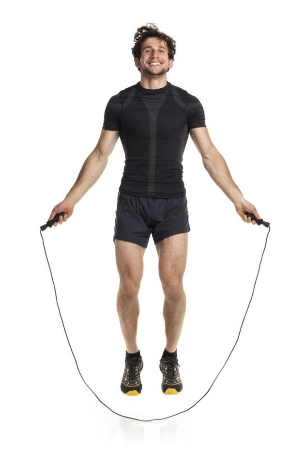 Athletic attractive man jumping on a rope on the white background