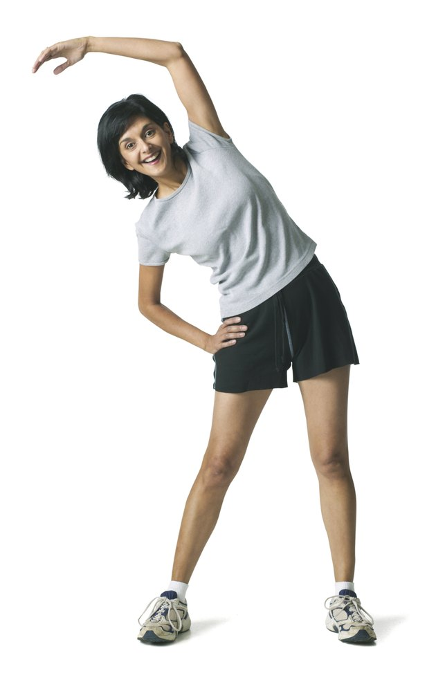 full body shot of an adult woman in a workout outfit as she warms up and stretches
