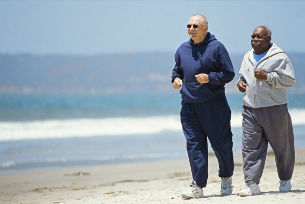 two mature men jogging on the beach