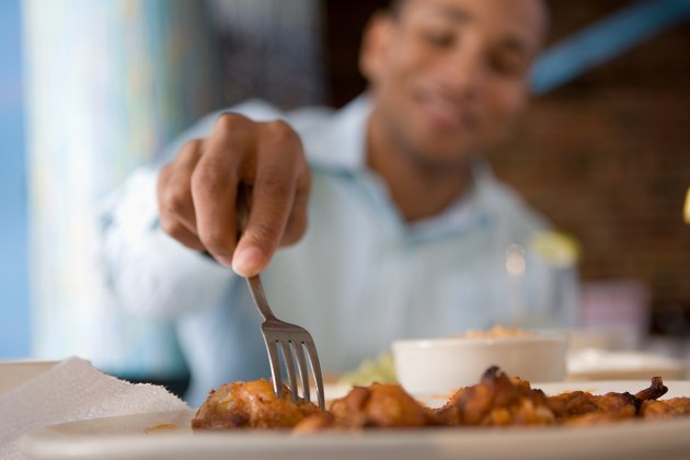 Man reaching for buffalo wing with fork
