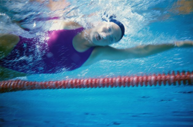 Low angle view of a young woman swimming underwater in a swimming pool