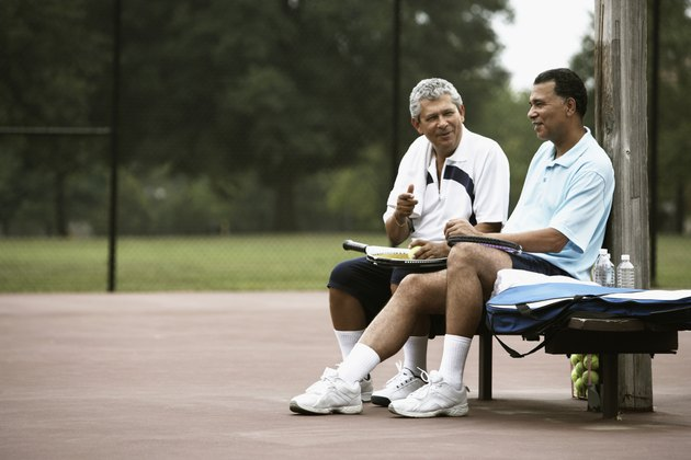 Multi-ethnic men talking on tennis court