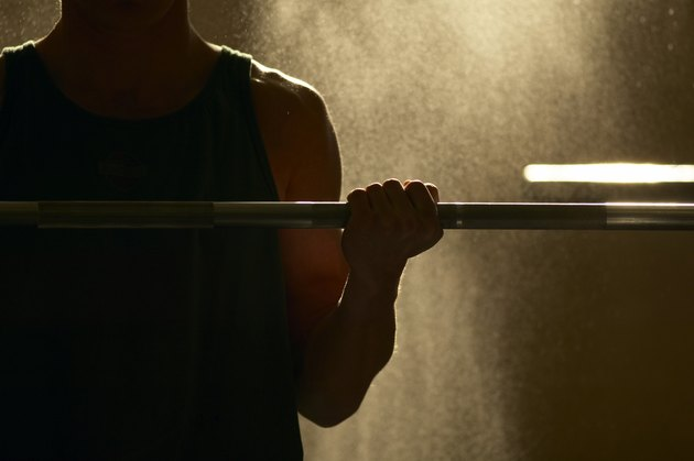 Mid section view of a man exercising with a barbell