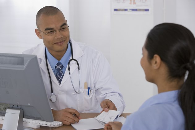 Male doctor handing prescription to patient